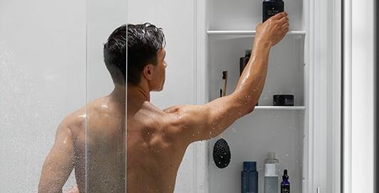 A man in a shower reaches for a bottle in a shower locker shelf.