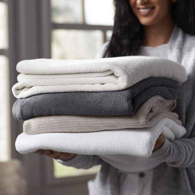 woman holding stack of bath towels