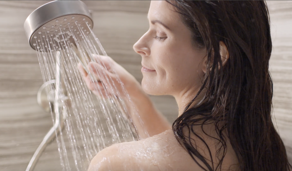 A woman uses a handshower to massage her shoulders in the shower.