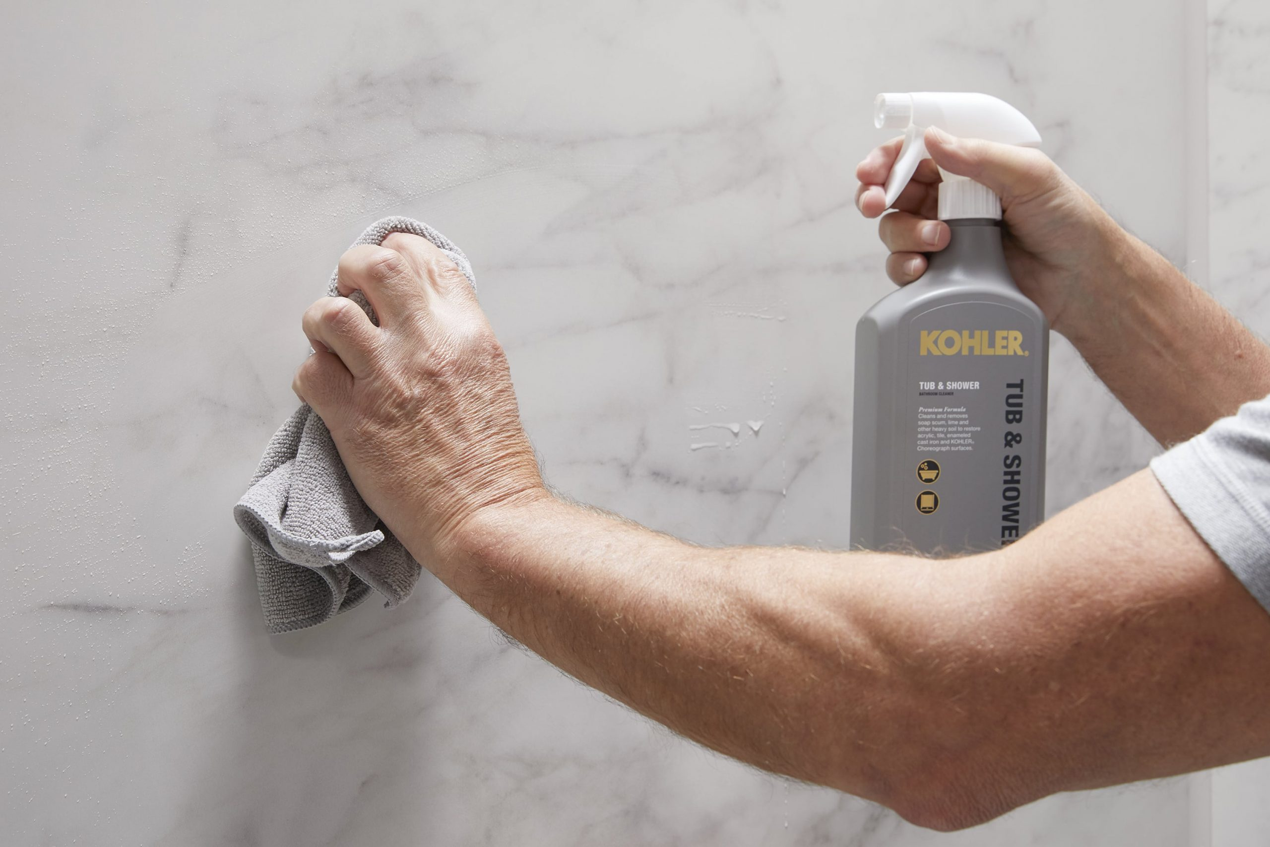 Photo of model cleaning LuxStone walls with KOHLER Cleaners