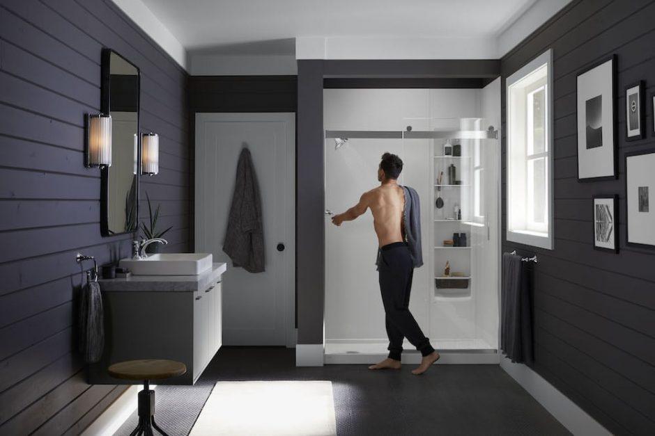 Man in a bathroom walking into a Kohler LuxStone Shower