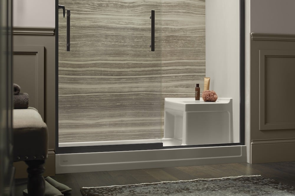 Shower base with glass door and shower seat.
