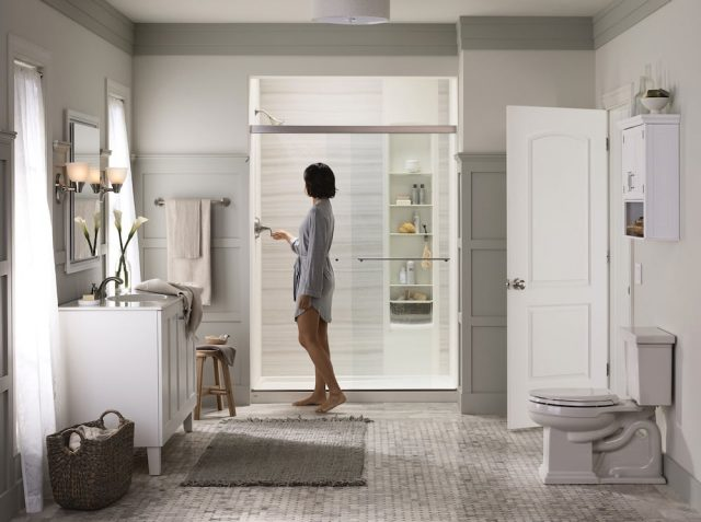 Woman standing outside her LuxStone shower.