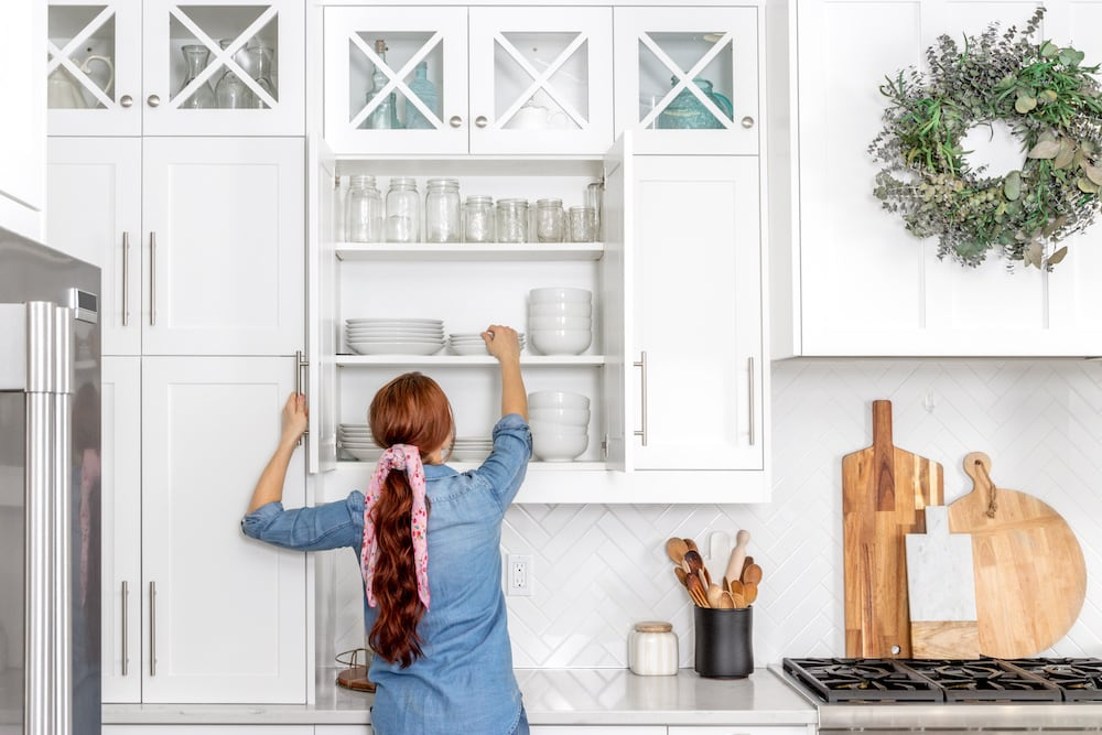 Woman in a bright white kitchen reaching into a cupboard to take out a plate'