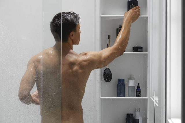 man reaching for bottle of shampoo