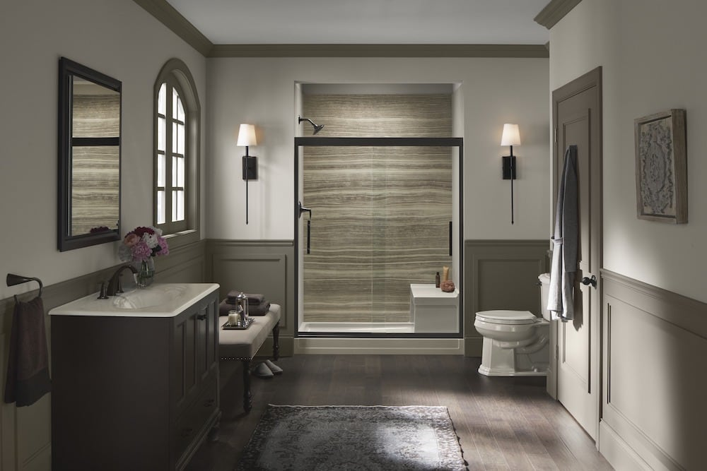 Walk-in shower with brown walls and dark hardware'