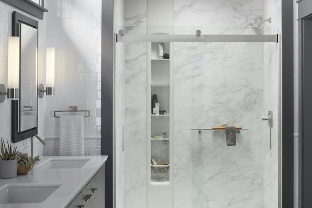 A bathroom with a Kohler LuxStone Shower that has gray and white Calacatta shower walls