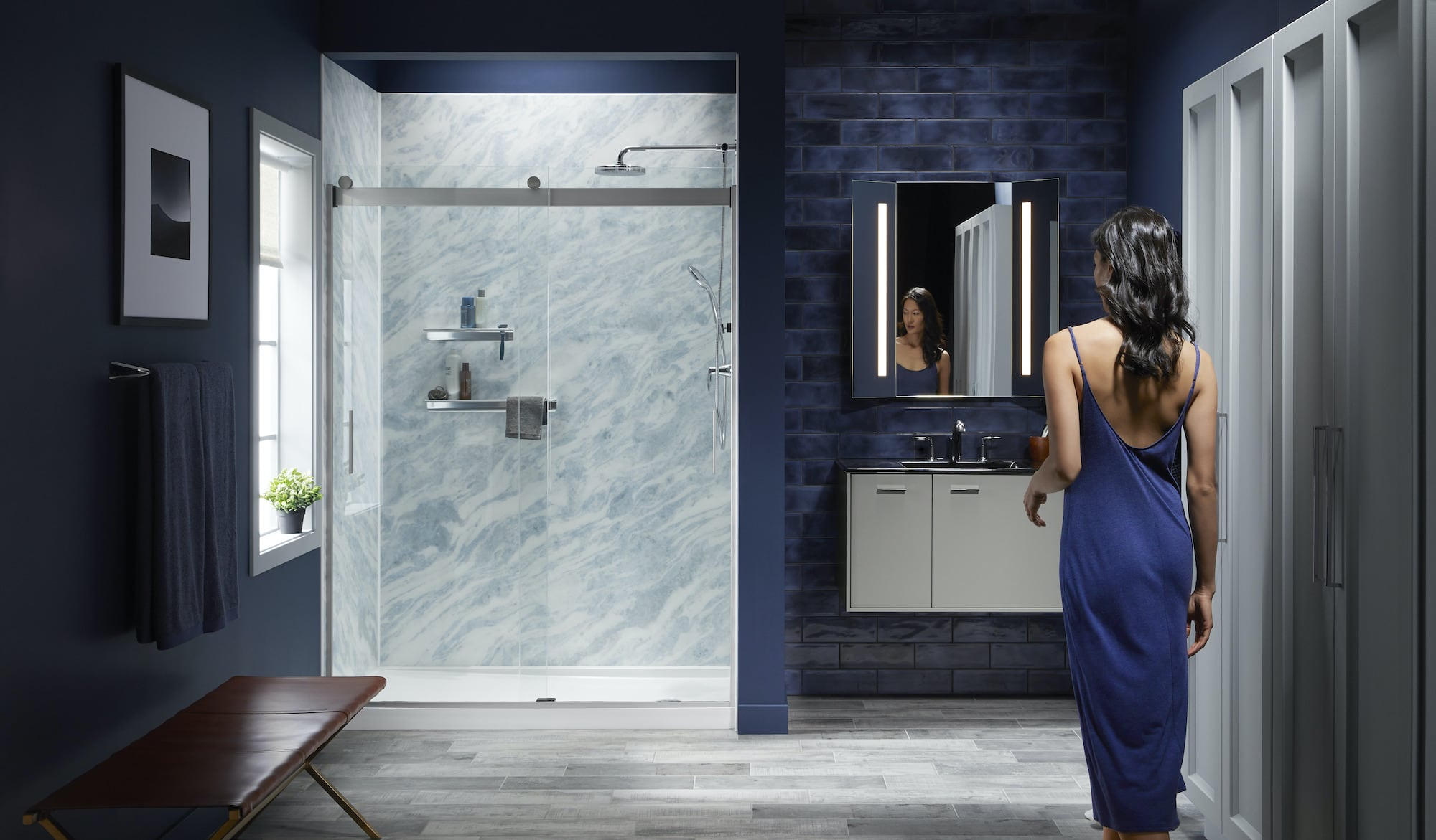 Woman entering bathroom with Bluette LuxStone shower walls'