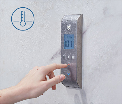 Hand pressing button on digital shower system remote.