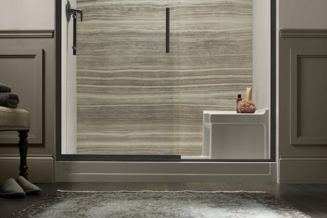 Shower with tan walls and white shower base with shower seat