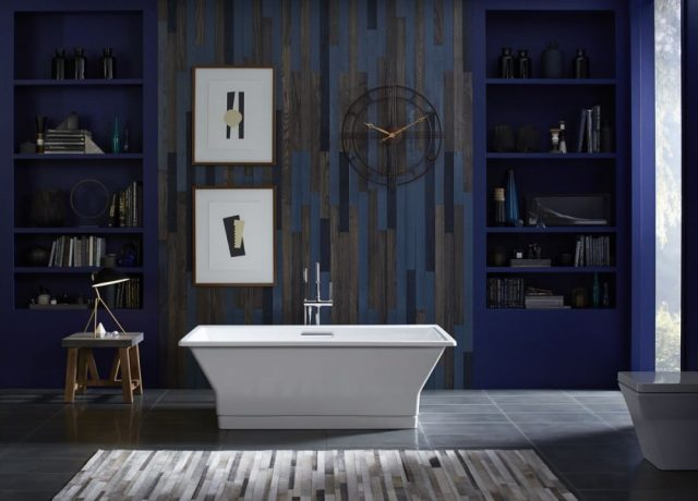 Dark blue bathroom with freestanding tub and wall hangings and shelving.