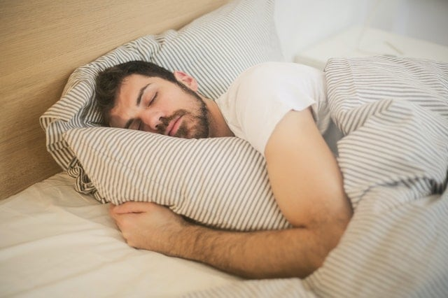 Man sleeping in bed with blanket and pillow