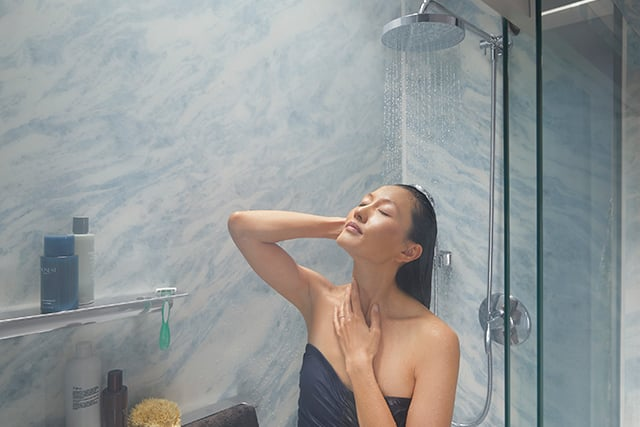 woman deep conditions hair in shower