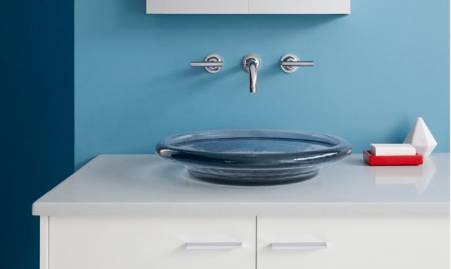 Bathroom sink with blue wall and red soap dispenser