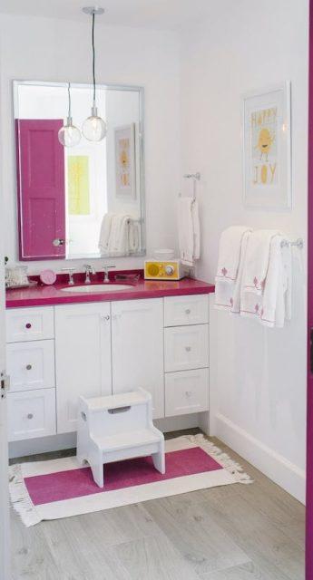 Magenta pink kids' bathroom with step stool and towel storage