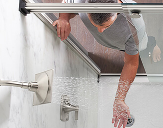 A man checking the water in a Kohler Shower