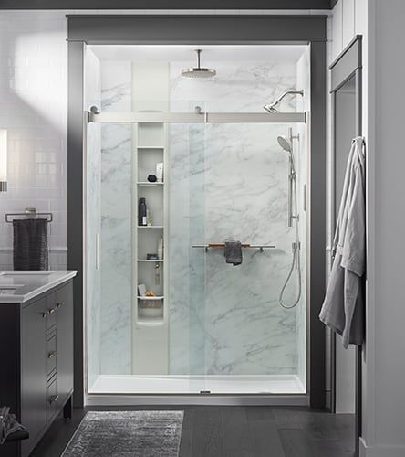 A modern bathroom with a Kohler LuxStone shower with multiple faucets